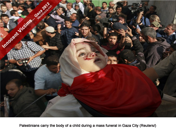 Palestinians carry the body of a child during a mass funeral in Gaza City